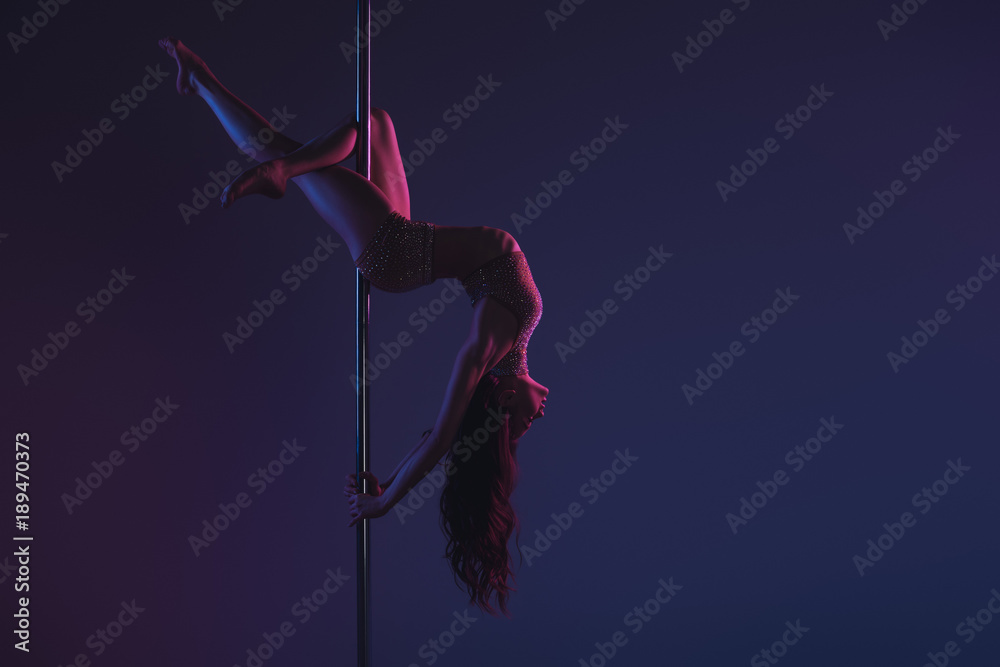 Fototapeta beautiful sensual flexible girl exercising with pole on blue
