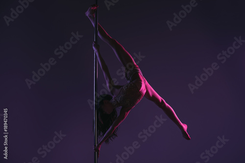 full length of athletic flexible young woman exercising with pole on blue Fototapeta