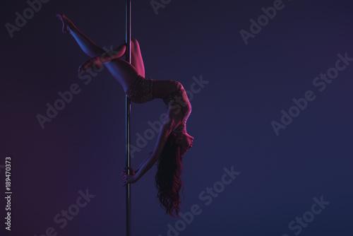 Fotografia  beautiful sensual flexible girl exercising with pole on blue