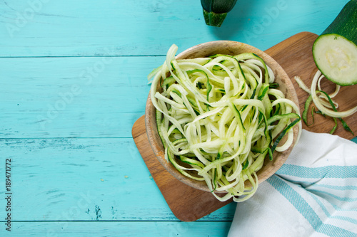 Raw zucchini noodles on a turquoise background