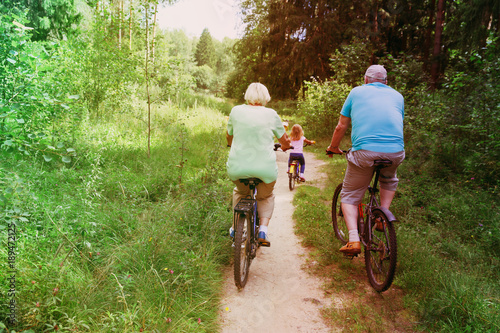 Fotografia  active senior couple with little granddaughter riding bikes in nature