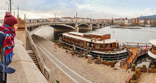 A woman looks from the dock to the Vltava River and moored ships restaurants Wallpaper Mural