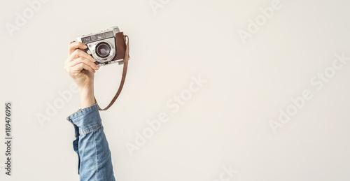 Fototapeta Raised up, arm holding vintage camera isolated background obraz na płótnie