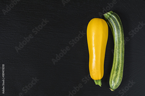 Striped fresh green zucchini and yellow zucchini on a black stone surface.  Top view, copy space. Healthy eating concept.
