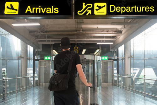 Man in travel with suitcase in front of billboards of departures and arrival in Canvas Print