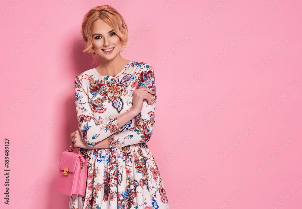 Fototapety, obrazy: Fashion photo of a beautiful elegant young woman in a pretty dress with flowers holding handbag posing over pink background. Fashion photo