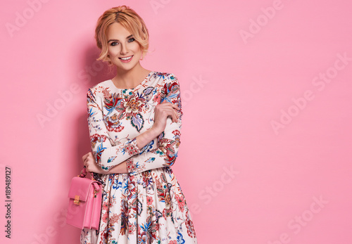 Fashion photo of a beautiful elegant young woman in a pretty dress with flowers holding handbag posing over pink background. Fashion photo