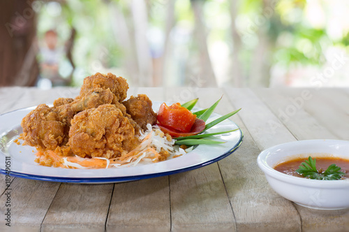 Foto op Aluminium Kip Fried chicken wing stick with coating flour in white dish and sweet chicken sauce on brown wooden table in green garden
