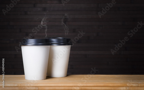 Foto auf AluDibond Kaffee two disposable white glasses of smoking coffee on a black wooden background