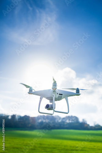 Picture of flying white drone camera in front of trees Wall mural