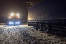 A Real Accident. Truck Traffic Accident At Night, On A Snowy Winter Road. Strongly Illuminated Wrecker Truck Pulls A Truck Out Of Snow Hanging.