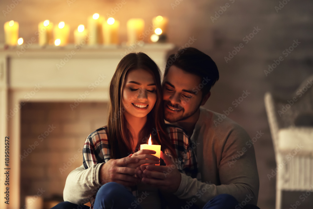 Fototapety, obrazy: Happy young couple with burning candle at home