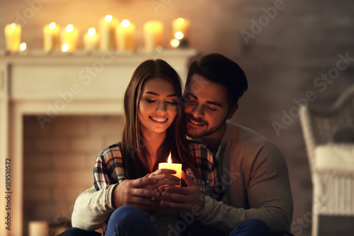 Happy young couple with burning candle at home