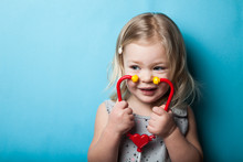 European Little Girl With Toy Stethoscope In Hands On A Blue Background.