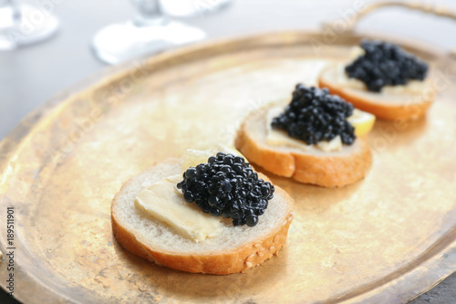 Tasty sandwiches with black caviar on metal tray