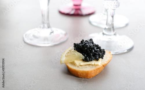 Tasty sandwich with black caviar and lemon on table
