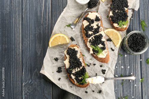 Tasty sandwiches with black caviar on table