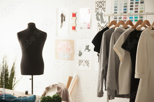 Fashion creative design studio cozy interior concept with mannequin dummy and exclusive unique stylish fashionable trendy clothes on hangers, dressmaking workplace, tailor shop, sewing workshop