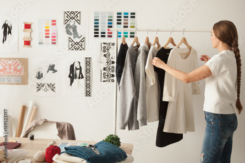 Female fashion designer works on new womenswear collection for clients in cozy w Fototapeta