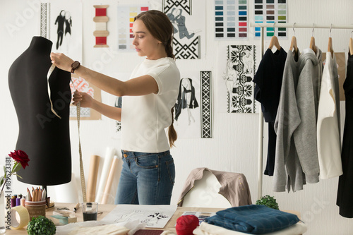 Valokuva Woman fashion designer measuring mannequin, seamstress holding tape working with