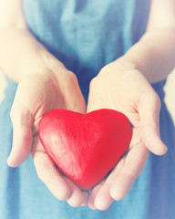 Heart in girl's hands, close up