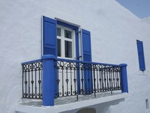 Blue Balcony On Traditional Whitewashed House In Greece
