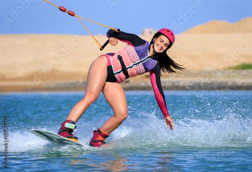 Wake boarding female sportsman beautiful girl with long black hair, sexy short wetsuit bikini, life style, recreation hobby fun, rider woman model posing on the seashore of the Red Sea