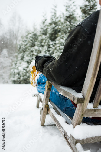 Photo  older man sitting in deck chair in a snow storm drinking a beverage