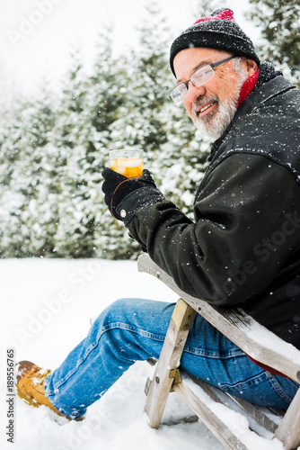 older man sitting in deck chair in a snow storm drinking a beverage Canvas Print