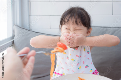 Valokuva  Little asian girl refuse toeat tomato in spagethi from her mother