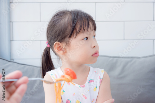 Leinwand Poster Little asian girl refuse toeat tomato in spagethi from her mother