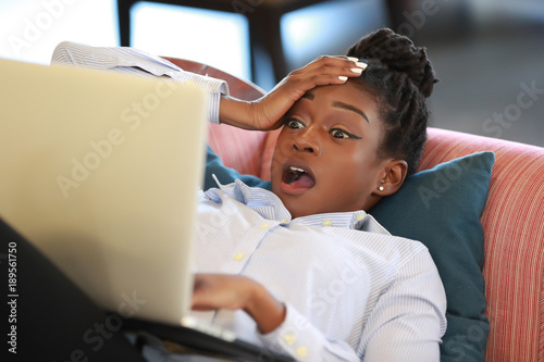 Woman watching laptop in disbelief Canvas Print