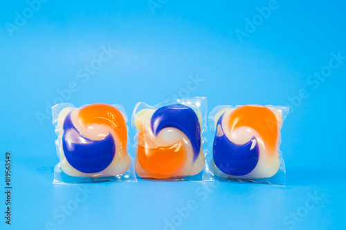 Fotomural  Laundry detergent pod capsules a on a blue background