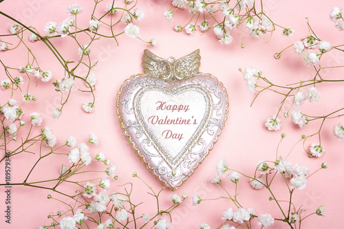 Foto op Canvas Bloemen Peculiar heart with felicitation and small white flowers on pink background.