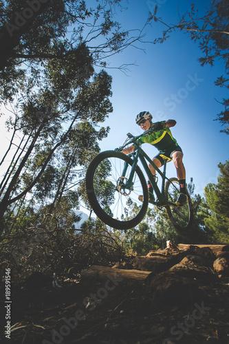 Fotografía  Wide angle view of a mountain biker speeding downhill on a mountain bike track i