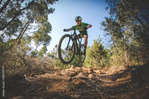 Stampa su Tela Wide angle view of a mountain biker speeding downhill on a mountain bike track i
