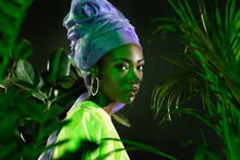 Attractive African American Woman In Traditional Wire Head Wrap Under Green Light Behind Leaves Looking At Camera