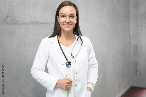 Obraz Uśmiechnięta młoda lekarka w białym kitlu - fototapety do salonu