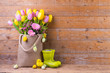 Easter decoration with tulip flowers in a bag and easter eggs on rustic wooden background