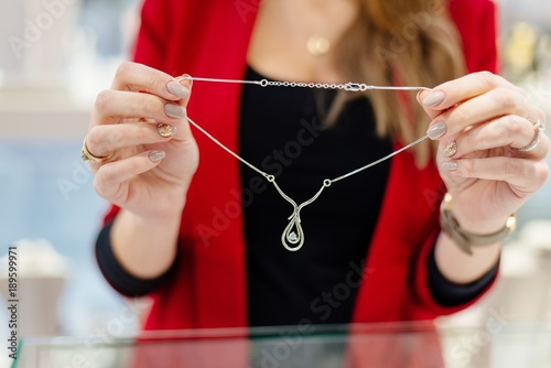 Woman owner of jewelry shop presenting necklace