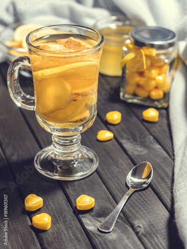 Spoed Foto op Canvas Chocolade Tea with ginger and lemon in a glass cup and yellow sweets on a wooden background