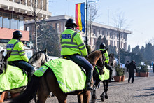 Local Police In Green Uniform On Horses Patrolling