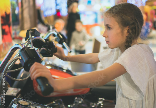 Zdjęcie XXL Mała dziewczynka bawić się motocykl symulator grę w parku tematycznym.