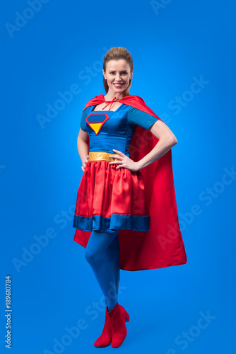 beautiful smiling woman in superhero costume standing akimbo isolated on blue Fototapeta