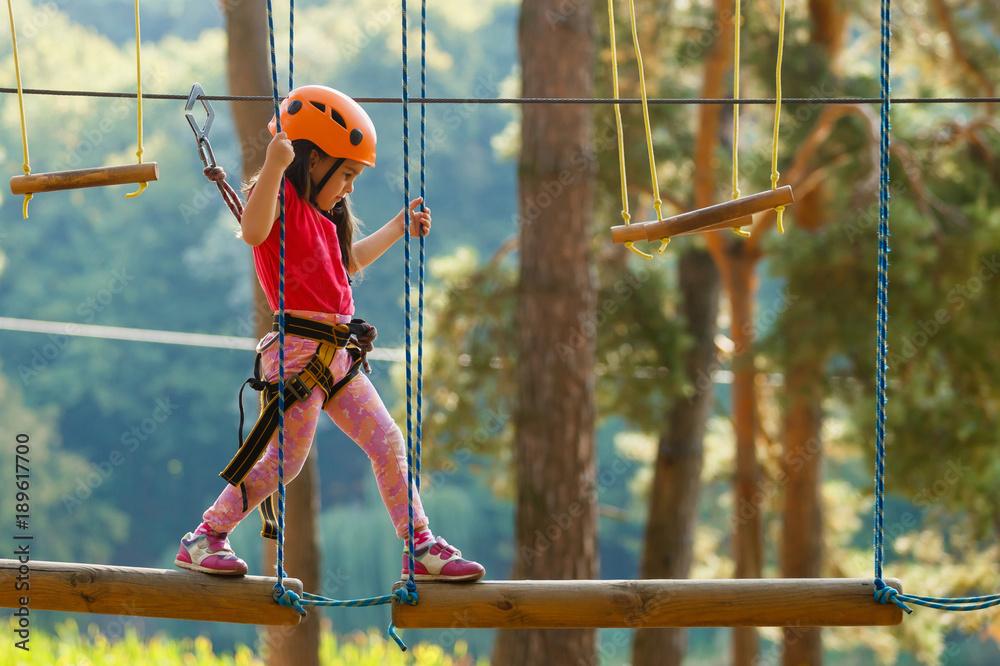 Fototapeta Portrait of cute little boy and girl walk on a rope bridge in an adventure rope park.
