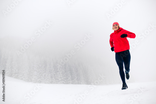 Leinwand Poster  Trail running woman on snow in winter mountains