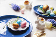 easter holiday festive dining table with golden metallic cutlery and eggs, hyacinth and tulip bouquet, blue and white plates. Celebration concept