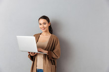 Portrait Of A Happy Young Asian Woman Holding Laptop