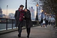 Couple Walking Along South Bank On Winter Visit To London