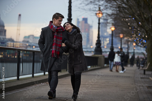 Photo  Couple Walking Along South Bank On Winter Visit To London